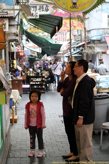 A family ponders the menu of a local fruit juice stand